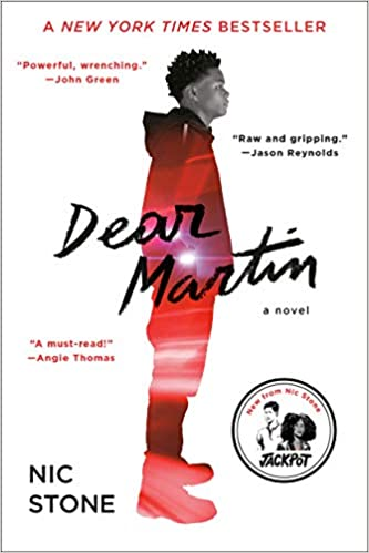 Book cover of Dear Martin by Nic Stone. With a white cover, an older teenage black boy is seen in profile. He is dressed in a hoodie and and pants with red right shining in as if it was part of a background.