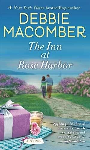 Book cover of The Inn at Rose Harbor by Debbie Macomber. A couple walks down a stone pathway towards the harbor.